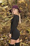 Blonde woman poses in black dress and boots. Young blonde woman in stunning black dress and over the knee boots wears a colorful hat in the autumn woods - fall stock images