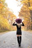 Blonde woman poses on country lane in fall. Young blonde woman in stunning black dress and over the knee boots wears a colorful hat standing on deserted country stock photos