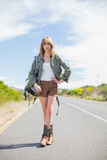 Sexy blonde woman posing while hitchhiking. On a deserted road in summertime Stock Photography