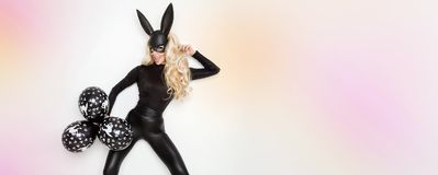 blonde woman posing in rabbit black mask and bodysuit