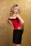 Sexy blonde woman in red corset and skirt. On golden background Royalty Free Stock Photo