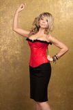 Sexy blonde woman in red corset and skirt. On golden background Royalty Free Stock Image