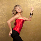 Sexy blonde woman in red corset and skirt. On golden background Stock Photos