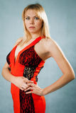 Sexy blonde woman in red dress. Standing on blue background Stock Photos