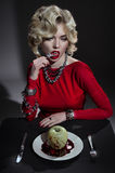 Sexy blonde woman in red dress with bloody apple Royalty Free Stock Images