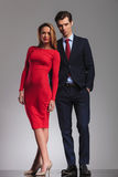 Sexy blonde woman in red dress standing next to  businessman Stock Images