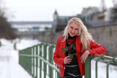 Blonde woman in red leather jacket. Beautiful young woman holding a red rose in winter time stock image