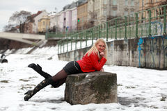 Sexy blonde woman in red leather jacket and mini skirt. Beautiful young woman laying on a rock in winter time Royalty Free Stock Photo