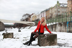 Sexy blonde woman in red leather jacket and mini skirt. Beautiful young woman sitting on a rock in winter time Royalty Free Stock Photo