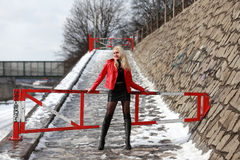 Sexy blonde woman in red leather jacket and mini skirt. Beautiful young woman standing in front of a gate in winter time Royalty Free Stock Photos