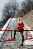 Sexy blonde woman in red leather jacket and mini skirt. Beautiful young woman standing in front of a gate in winter time Royalty Free Stock Image