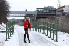 Sexy blonde woman in red leather jacket and mini skirt. Beautiful young woman standing on a snowy street in winter time Royalty Free Stock Photography