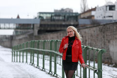 Blonde woman in red leather jacket and mini skirt. Beautiful young woman standing on a snowy street in winter time stock images