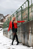 Sexy blonde woman in red leather jacket and mini skirt. Beautiful young woman standing at a wall with graffiti in winter time Royalty Free Stock Photo