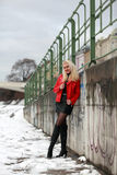 Sexy blonde woman in red leather jacket and mini skirt. Beautiful young woman standing at a wall with graffiti in winter time Stock Images