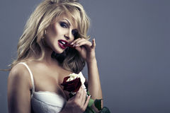 close-up portrait of beautiful blonde woman with red - white rose royalty free stock images