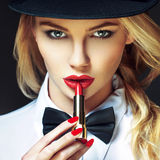 Sexy blonde woman with red lips and nails applying lipstick Royalty Free Stock Images