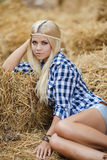 Sexy blonde woman resting on hay in rural areas. Sexy fashion woman in cow girl country style on hay stack. Beauty romantic girl outdoors against hay stack Stock Photography