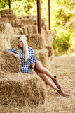 Sexy blonde woman resting on hay in rural areas. Sexy fashion woman in cow girl country style on hay stack. Beauty romantic girl outdoors against hay stack Stock Image