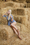 Sexy blonde woman resting on hay in rural areas Royalty Free Stock Image