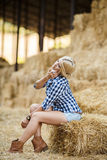 Sexy blonde woman resting on hay in rural areas. Sexy fashion woman in cow girl country style on hay stack. Beauty romantic girl outdoors against hay stack Royalty Free Stock Photo