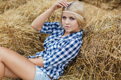 blonde woman resting on hay in rural areas Royalty Free Stock Images