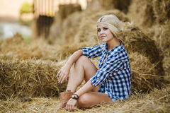 Sexy blonde woman resting on hay in rural areas. Sexy fashion woman in cow girl country style on hay stack. Beauty romantic girl outdoors against hay stack Stock Photo