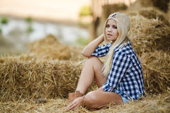 Sexy blonde woman resting on hay in rural areas. Sexy fashion woman in cow girl country style on hay stack. Beauty romantic girl outdoors against hay stack Royalty Free Stock Image