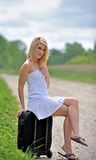 Sexy blonde woman sitting by the road Royalty Free Stock Photography
