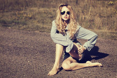 Blonde Woman Sitting on the Road Stock Photo