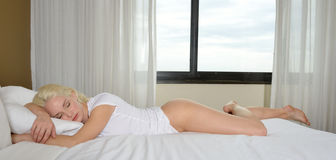 Sexy blonde woman sleeps in bed Royalty Free Stock Photos