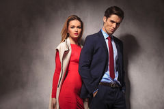 Blonde woman standing behind her man. Blonde women in red dress and long coat standing behind her men in suit and tie stock photos