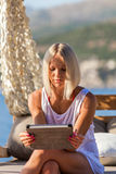 Sexy blonde woman with tablet relaxing on the beach. Stock Images