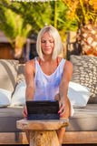 blonde woman with tablet relaxing on the beach. Stock Photos