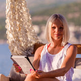 blonde woman with tablet relaxing on the beach. Stock Images