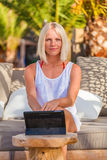 Sexy blonde woman with tablet relaxing on the beach. Stock Photography