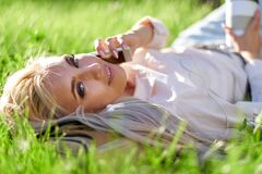 Free Sexy Blonde Woman Talking On The Mobile Phone And Lying On Meadow Stock Photo - 180870250