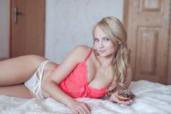 blonde woman in underwear holding doughnut Stock Photos