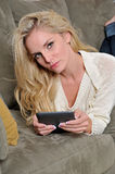 Sexy blonde woman using tablet computer / e-reader Stock Photography