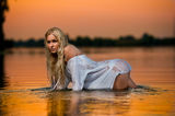 blonde woman in water at sunset Stock Photography