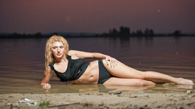 Sexy blonde woman in water after sunset Royalty Free Stock Photography