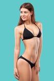 Sexy blonde woman wearing swimwear posing on color background. Perfect body. Bikini catalogue. Stock Photos