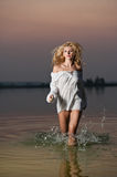Sexy blonde woman in white blouse in a river water Royalty Free Stock Images