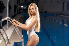Sexy blonde woman in white swimsuit. Stunning sexy blonde woman with blue eyes dressed in white deep plunge swimsuit standing against swimming pool on background Stock Photography