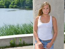 Blonde woman - white tank and jean shorts. Blonde woman in white tank top and denim cut-off shorts standing next to lake in front of pillar - summer royalty free stock photo
