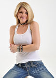 Blonde woman in white tank and jeans. Blonde woman in white tank and blue jeans on her knees - smiling - wearing choker collar stock images