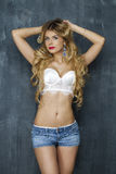 Sexy blonde woman in white underwear on a dark wall Royalty Free Stock Image