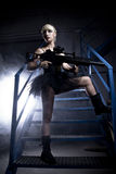 Sexy blonde young, holding a machinegun in an industry area Stock Photo