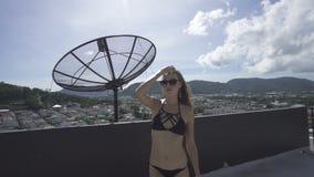 Sexy blonde Zauberfrau, welche die schwarze Badebekleidung aufwirft auf einer Dachspitze an einem sonnigen Sommertag mit Luft- un stock video