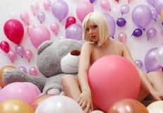 Sexy blonder Aufstellungsakt im Studio mit Ballonen Stockbild
